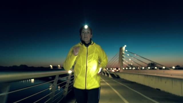 slo mo 女橋を渡ってジョギングしながら音楽を再生するためにスマート フォンを準備 - 30代の女性一人点の映像素材/bロール