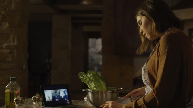 woman preparing and eating salad while watching digital tablet in kitchen / cedar hills, utah, united states - making salad stock videos & royalty-free footage