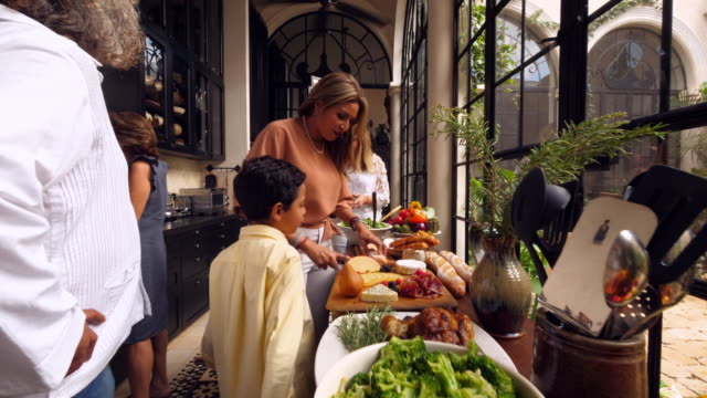 ms woman preparing appetizers in kitchen during family celebration - real people stock videos & royalty-free footage