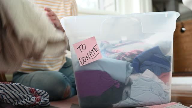 vídeos de stock, filmes e b-roll de woman preparing box to donate - só uma mulher de idade mediana