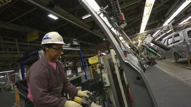 MS Woman preparing door for installation on minivan in an auto assembly plant / Princeton, Indiana, United States