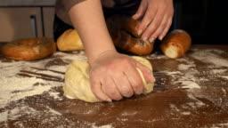 Woman preparing dough in a kitchen, slow motion.