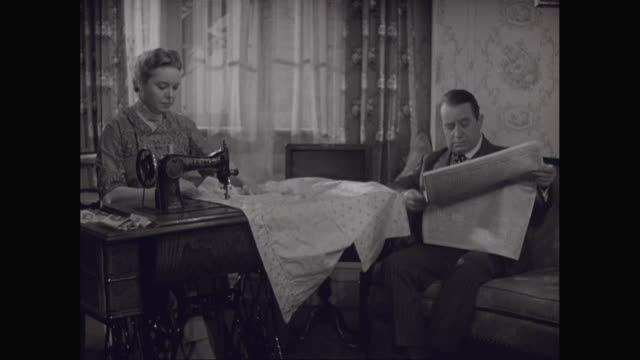 MS Woman preparing in sewing machine with man reading newspaper on sofa / United States