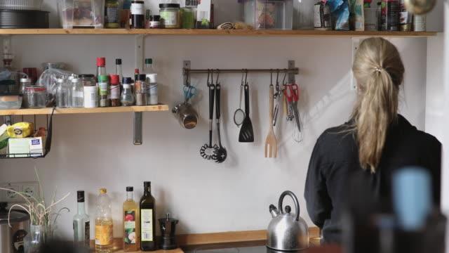 woman preparing morning coffee in kitchen at home - solo una donna di età media video stock e b–roll