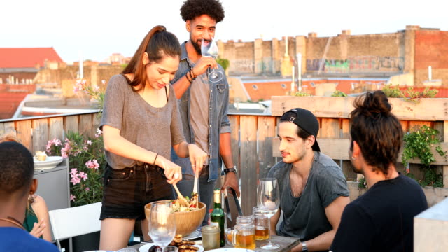 Woman preparing pasta amidst friends on rooftop