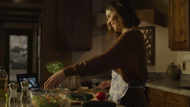 woman preparing salad and watching digital tablet in kitchen / cedar hills, utah, united states - beautiful woman stock videos & royalty-free footage