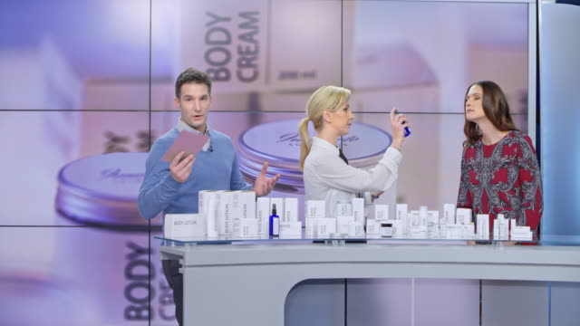 ld woman presenting a cosmetic line on the tv show spraying some perfume onto the female model while talking to the audience and the male host - advertisement stock videos & royalty-free footage