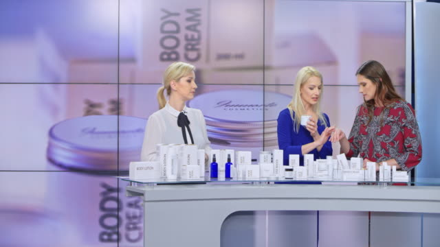 ld woman presenting a cream from her cosmetic line rubbing some on the female model's hand while the female tv show host is talking - advertisement stock videos & royalty-free footage