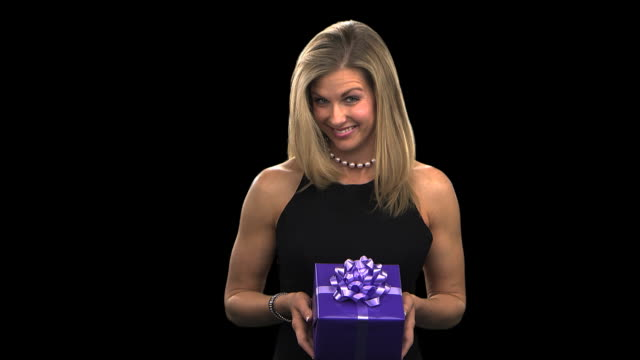 woman presenting a gift - this clip has an embedded alpha-channel - pre matted stock videos and b-roll footage