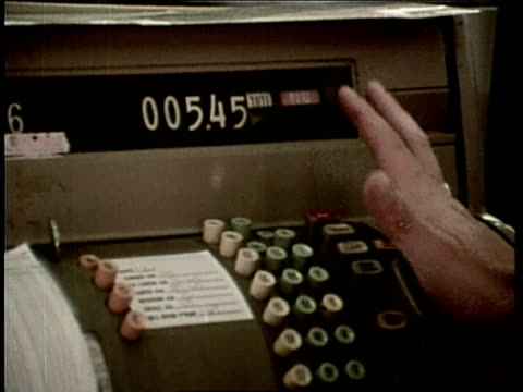 a woman presses a button on a cash register - cash register stock videos and b-roll footage
