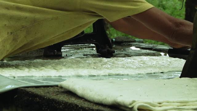 ms cu zo woman pressing latex with wooden roller beside mangle machine / ko samui, thailand - ラテックス点の映像素材/bロール