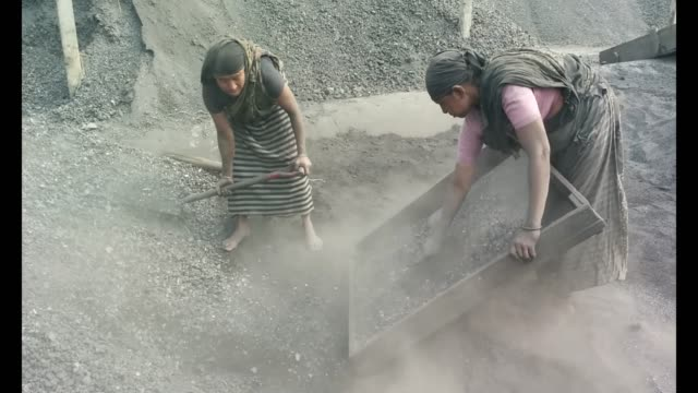 woman process waste coal to use it again these torn coal they collect from bricksfield - vita non sana video stock e b–roll