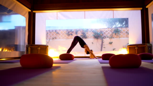 stockvideo's en b-roll-footage met woman professional yoga instructor practicing yoga on the empty class at sunset. - silvestre