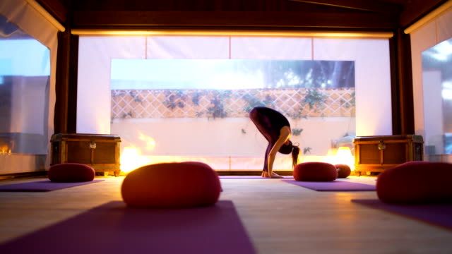 woman professional yoga instructor practicing yoga on the empty class at sunset. - sun salutation stock videos and b-roll footage