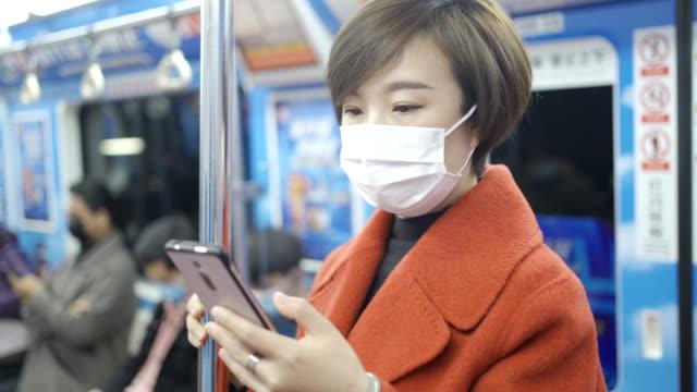 frau schützen sich vor dem covid-19 mit masken in der u-bahn - sms stock-videos und b-roll-filmmaterial
