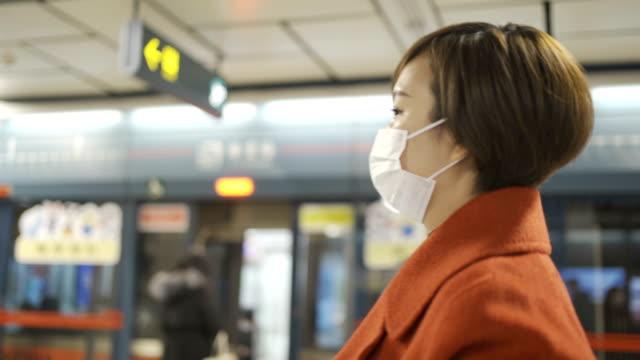 vídeos y material grabado en eventos de stock de mujer protegerse de la covid-19 con máscaras en el metro - china