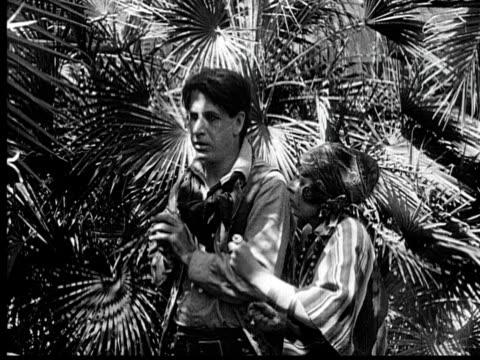 b/w 1920 ms woman pulling and biting man's hand in garden - fan palm tree stock videos & royalty-free footage
