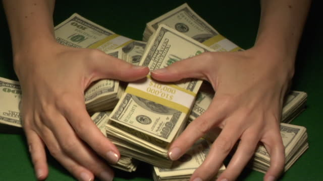CU, Woman pulling bunches of American dollar bills in paper bands on table, close-up of hands