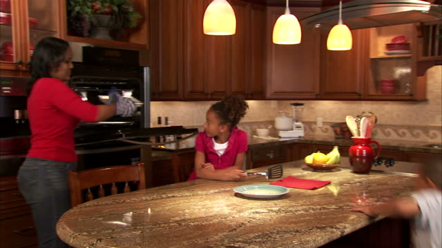 ws ds woman pulling cookies out of oven and setting them down by son (4-5) and daughter (6-7) in kitchen / salt lake city, utah, usa - oven mitt stock videos and b-roll footage
