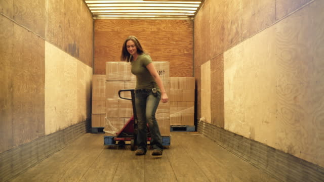 woman pulling hand held pallet truck and stock from elevator - hubwagen stock-videos und b-roll-filmmaterial