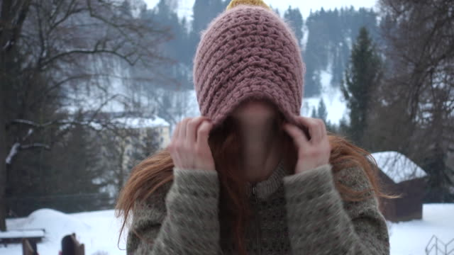 Woman pulling knitted hat over her face