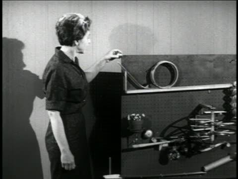 vidéos et rushes de b/w 1960 woman pulling lever on chain-reaction device / educational - levier de contrôle