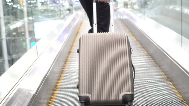 woman pulling luggage at airport - pulling stock videos & royalty-free footage