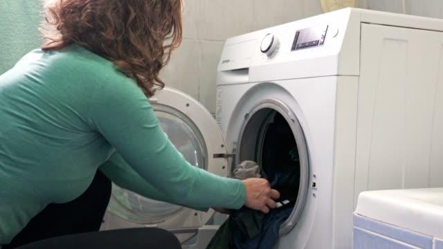 vidéos et rushes de femme tirant sur le linge de la machine à laver et dans le panier, il est maintenant temps pour accrocher le linge - faire sa toilette