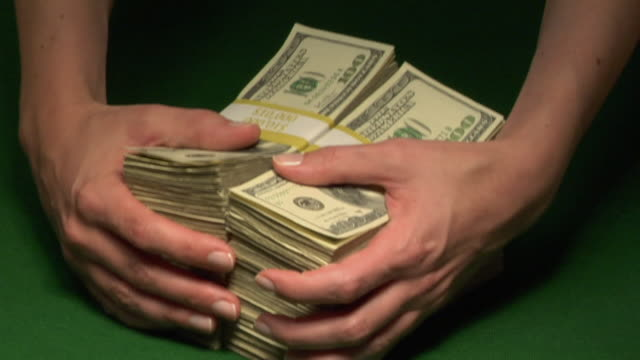 CU, Woman pulling two stacks of American dollar bills in paper bands on table, close-up of hands