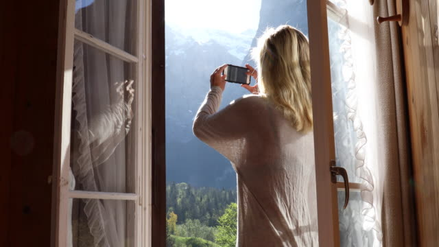 Woman pulls doors open to reveal mountain landscap