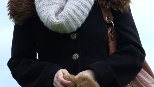 A woman pulls on a pair of mittens
