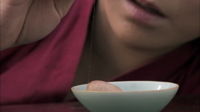 Woman pulls silk thread from cocoon in bowl.