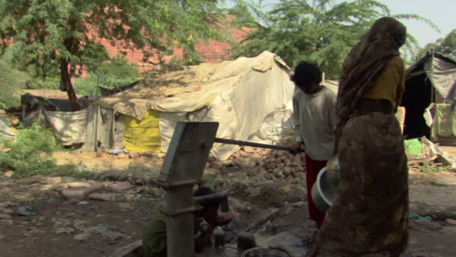 cu zo tu ws woman pumping water from well and carrying jug on head, agra, uttar pradesh, india - village stock videos & royalty-free footage