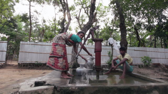 a woman pumping water into a bucket in a village not far from srimangal, sreemangal (srimangal), division of sylhet, bangladesh, indian sub-continent, asia, indian sub-continent, asia - water pump stock videos & royalty-free footage