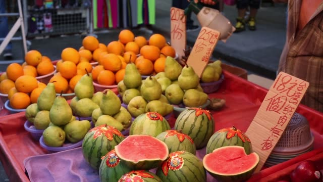 a woman purchases fruit from a market stall in the mong kok district of hong kong apples and melons are displayed for sale at market stall a market... - mong kok stock videos and b-roll footage
