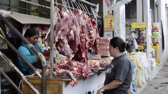 MS Woman purchasing meat at shop / Otavalo, Ecuador