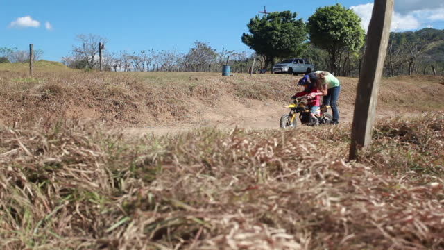 a woman pushes a dirt bike for a young boy on a dirt bike track, then the young boy gets on it while the woman talks to him on a sunny summer day - kelly mason videos stock videos & royalty-free footage
