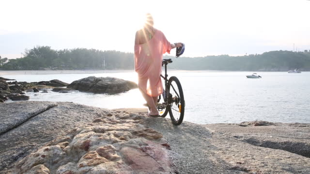 Woman pushes bicycle across rock slabs, looks out to sea