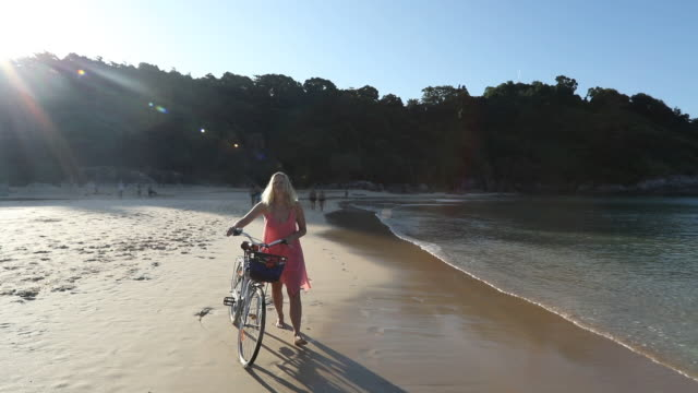 Woman pushes bicycle along tropical beach