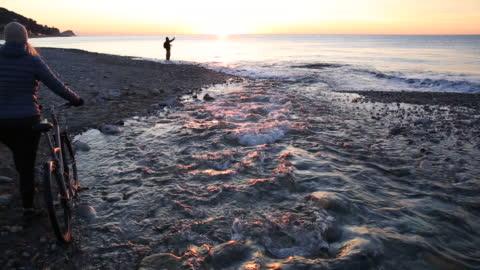 vídeos y material grabado en eventos de stock de mujer empuja a bicicleta a lo largo de borde del río de playa al amanecer - one mature woman only