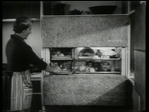B/W woman pushes button to open refrigerator / Raises countertop / SOUND