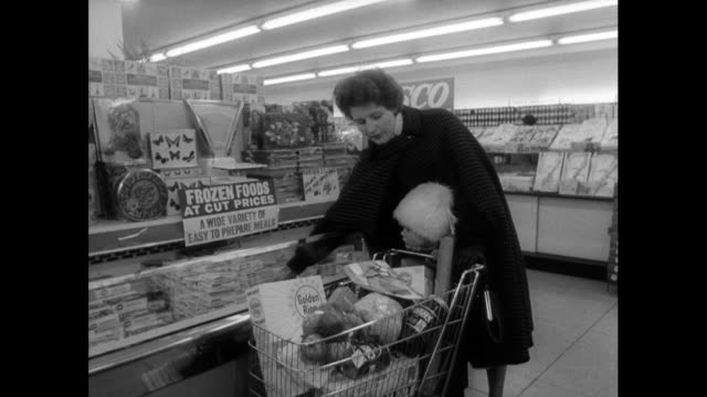 woman pushes child and trolley around supermarket; 1963 - cibi surgelati video stock e b–roll