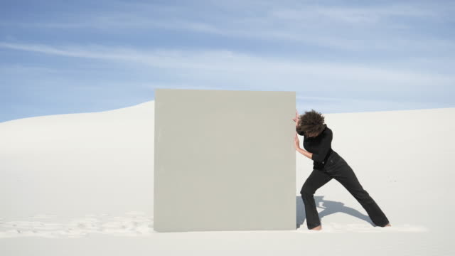 woman pushes grey portal in desert, medium shot - schieben stock-videos und b-roll-filmmaterial