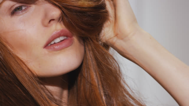 vidéos et rushes de woman pushes hand through her red hair to cover parts of her face creating volume, movement and a tousled look - cheveux