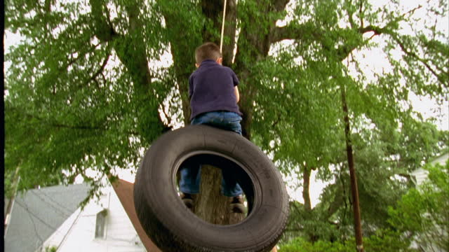 a woman pushes her son on a tire swing. - reifen stock-videos und b-roll-filmmaterial