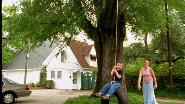 vídeos y material grabado en eventos de stock de a woman pushes her son on a tire swing. - cámara en mano