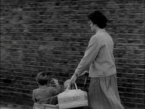 A woman pushes her two children in a pram along a suburban street