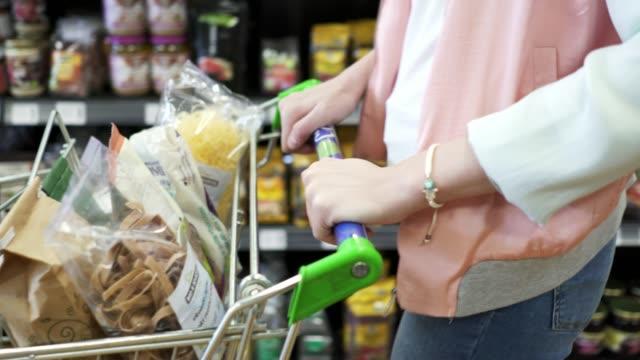 vidéos et rushes de femme poussant un shopping panier trought au supermarché - panier courses
