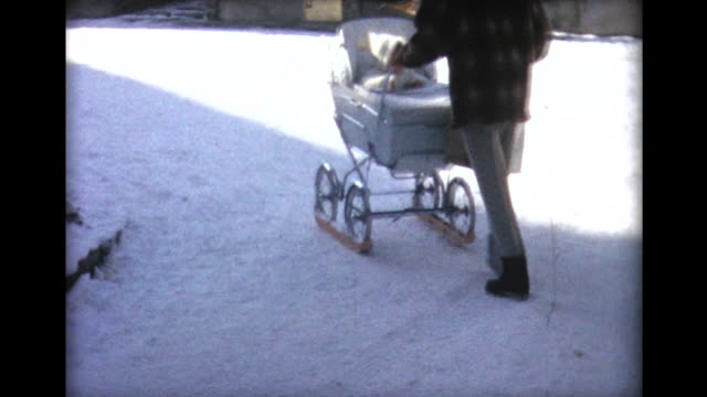 vídeos de stock, filmes e b-roll de 1963 woman pushing baby carriage fitted with skis through snow - home movie