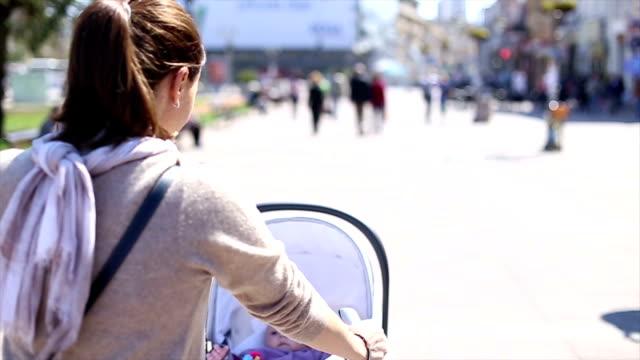 vídeos y material grabado en eventos de stock de mujer empujando cochecito para niños - cochecito de bebé